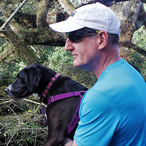 Doug Marting, Project Management MBA, with his dog in the woods